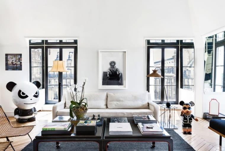 W salonie wrażenie silnego kontrastu wywołuje przede wszystkim graficzny rysunek okien. Projektantka wzmocniła efekt, wyklejając glify po bokach szyb i nad nimi lustrami. Powielają one pejzaże jednej z najstarszych dzielnic miasta. Sofę Yasmine zaprojektowała Sarah, stoliki kawowe są z XIX wieku.