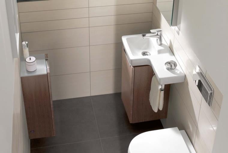 Wśród wyposażenia przeznaczonego specjalnie do małych łazienek i toalet znajdziemy sprzęty wielofunkcyjne. Oto jeden z nich: osadzona na szafce umywalka z dodatkowym blatem i uchwytem na ręcznik.