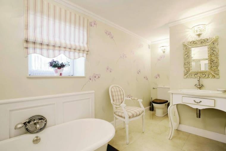 Dyskretnie, we wnęce<br/> Kącik z sedesem został urządzony w głębi łazienki, w sporej wnęce z szafą. Tradycyjny w formie model z drewnianą deską znakomicie komponuje się z wystrojem łazienki zaaranżowanej w stylu nawiązującym do rokokowych wnętrz - wystarczy spojrzeć na krzesło, szafkę pod umywalką, wiszące nad nimi lustro w bogato zdobionej ramie, a także na sztukateryjne listwy pod sufitem. Całe wnętrze jest utrzymane w stonowanej, jasnej kolorystyce.