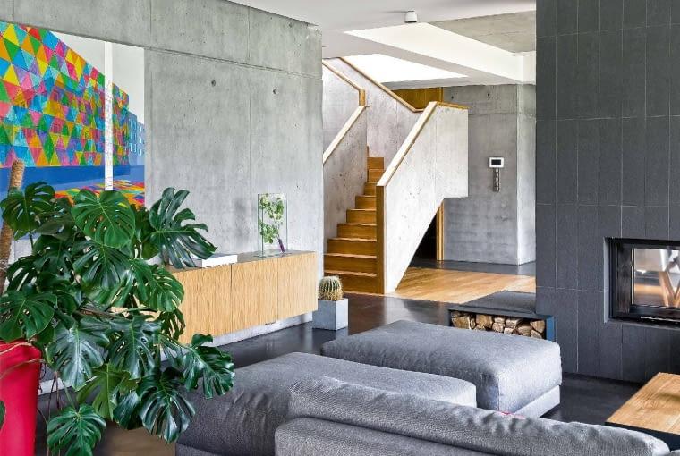 Architekci zpracowni ADHD wgłównej roli aranżacyjnej obsadzili beton, który wtym domu ujawnia całą gamę odcieni: inaczej wygląda na ścianch, inaczej na podłodze, balustradzie schodów czy kominku. Na pierwszym planie po lewej obraz Bartosza Głowackiego.