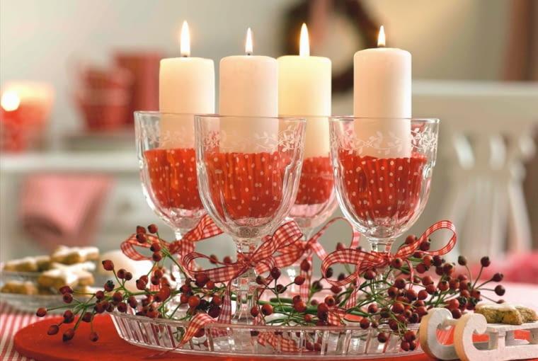 """Wieniec adwentowy """"W szkle"""". Kielichy ustawione na szklanej paterze wypełniono papilotkami z pergaminu. To praktyczne rozwiązanie, bo stopiona stearyna nie będzie brudzić szkła. U podstawy nagie gałązki róży wielokwiatowej z owocami"""