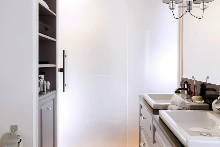 ŁAZIENKA. Drzwi i ścianka z matowego szkła zapewniają intymność (niezbędną w takim pomieszczeniu jak łazienka), a zarazem przepuszczają światło, doświetlając wnętrze.