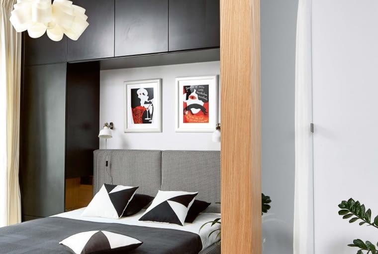W niewielkiej sypialni wykorzystano każdy centymetr. Ścianę, przy której stoi łóżko, zajmuje zrobiona na wymiar pojemna zabudowa, składająca się z dwóch wąskich szaf i górnych szafek. Łóżko (model Porto firmy Max-Fliz) zyskało zrobiony na zamówienie tapicerowany zagłówek. Kinkiety z IKEA dobrze sprawdzają się podczas czytania - strumień światła można kierować w dowolną stronę. Lampa sufitowa Loftlight o organicznych kształtach przyjechała z lampalampa.pl.