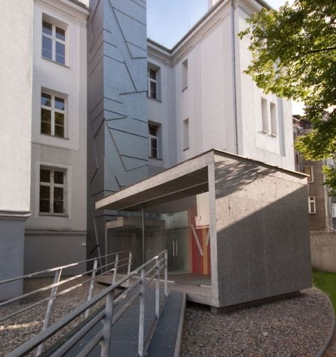 Pawilon z windą dla niepełnosprawnych przy bocznym wejściu do budynku Zespołu Szkół Ogólnokształcących nr 10 w Gliwicach.