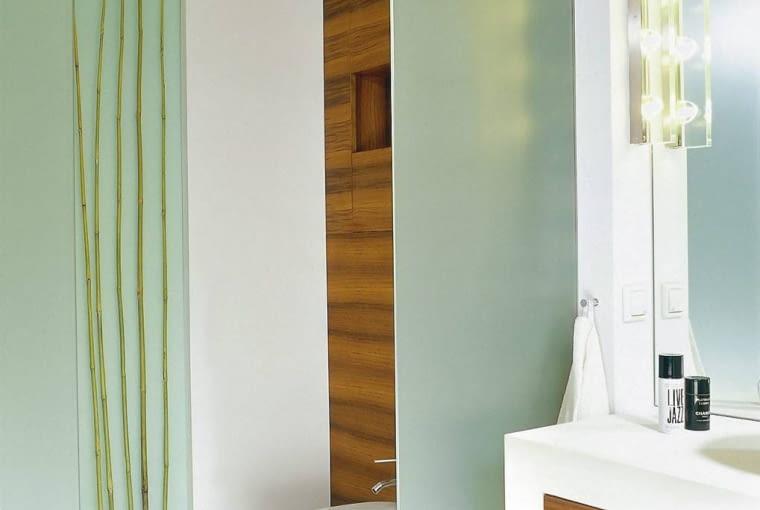 Na ścianach i podłodze zamiast płytek ceramicznych ułożono płytki wapienia. Jasny kamień i chłodne szkło kontrastują z ciepłym drewnem tekowym, którym wyłożono m.in. ściany nad sedesem i bidetem oraz front szafki z umywalką.