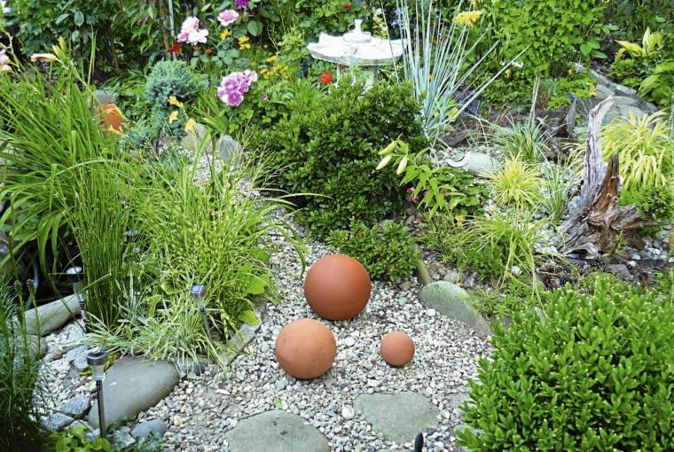 Na niewielkiej powierzchni ogródka mieszają się style - tutaj wyraźne są inspiracje ogrodem japońskim: żwirowa ścieżka, ozdobne trawy, elementy dekoracyjne z terakoty.