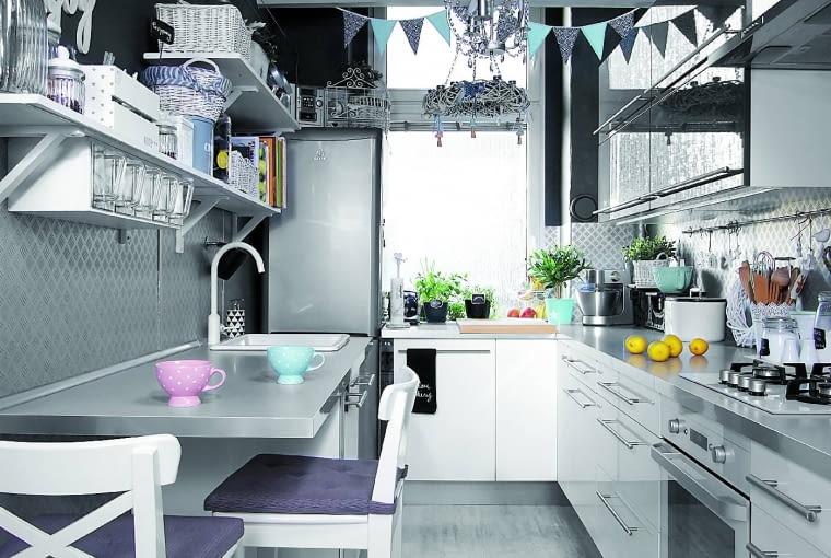 Ściany w kuchni od lat chroni wykładzina PCW. Miała być tymczasowo, ale ponieważ się sprawdziła, gospodarze zrezygnowali zpołożenia tam blachy. Sufit wwysokim pomieszczeniu obniżono izrobiono pawlacze, podtrzymywane przez efektowne belki. Przedłużony blat (z IKEA), w którym zamontowano niewielki ceramiczny zlewozmywak, pełni funkcję stolika śniadaniowego.