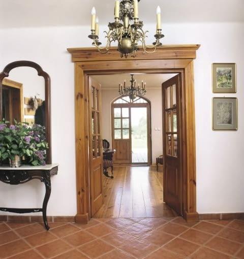 Sień prowadząca do salonu dzieli jednocześnie frontową część budynku na dwie strefy: gabinetową i jadalnianą