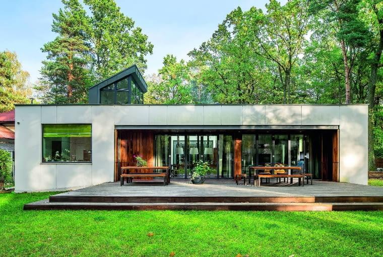Właściciele bardzo chcieli żyć w otoczeniu drzew i zieleni, bardzo też zależało im na tym, by stworzony przez nich dom nie przytłoczył tej zieleni swoimi gabarytami; dlatego zdecydowali się na dom parterowy i otwarty na otoczenie dzięki wielkim przeszkleniom