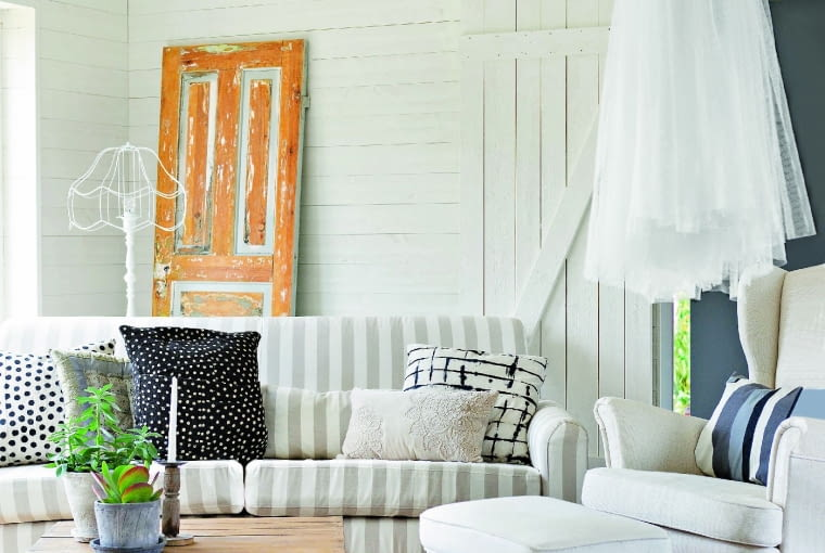 tWhite armchair and footstool and striped sofa around wooden table on castors in living room with white wood cladding