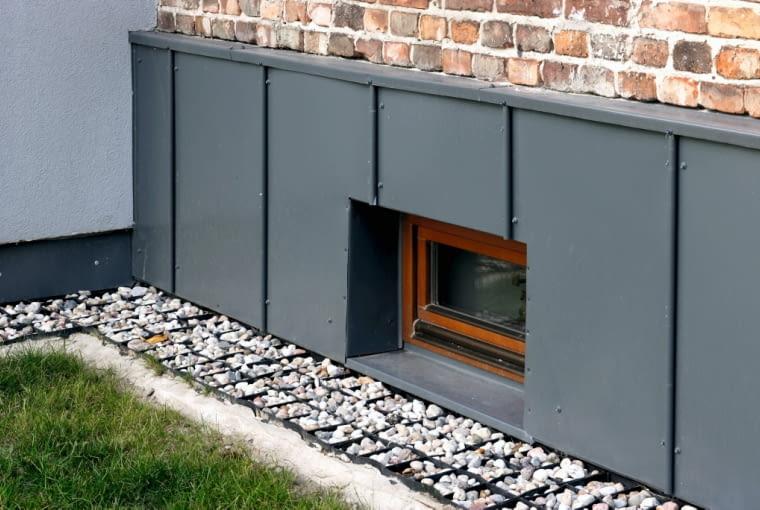Żwirowa opaska wokół budynku to rozwiązanie, które architekt stosuje przy większości remontowanych obiektów zamiast pękającego betonu