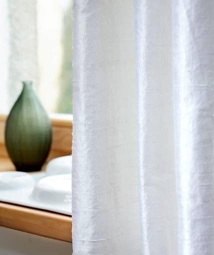 DEKORACJE OKIEN - DYSKRETNA PROSTOTA. Aby zasłony z surowego jedwabiu nabrały sztywności i lepiej się układały, podszyto je inną tkaniną. Dodatkowo chroni ona jedwab przed działaniem słońca.