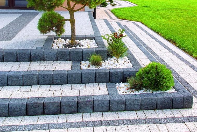 Schodki z regularnych betonowych kostek wykończonych kruszywem kamiennym.
