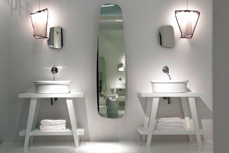 Kryształowo czysta biel, idealny porządek i żadnych zbędnych detali. Lustra i lampy o nieregularnej formie są efektownym akcentem. Więcej luster na falper.it