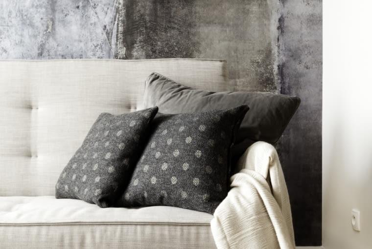 Tapeta o efektownym wzorze stanowi tło dla miękkiej sofy.