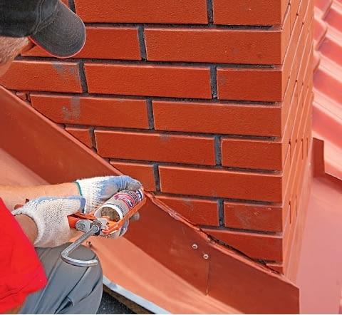 Krok 6. Miejsce osadzenia obróbki z blachy w ścianie komina dodatkowo uszczelnia się materiałem elastycznym - silikonem dekarskim.