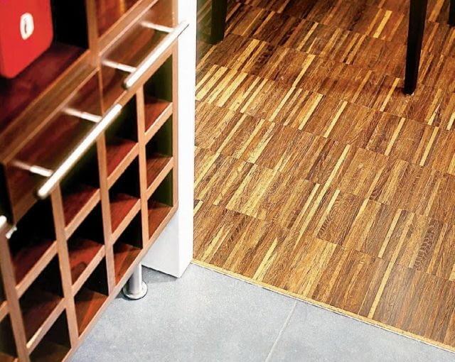 Połączenie drewna z ceramiką. Parkiet lamelowy oddzielono od płytek pasami korka i metalowym kątownikiem