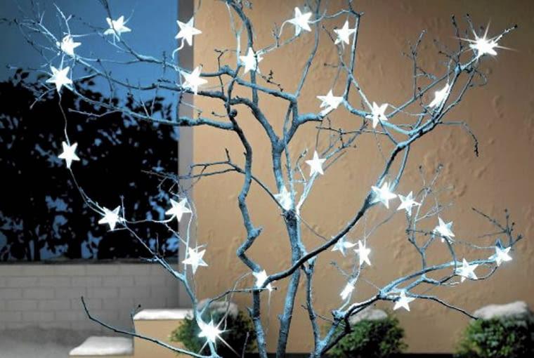 Odświętne oświetlenie ogrodu. Diodowy łańcuch świetlny z białych gwiazdek z przezroczystego tworzywa sztucznego