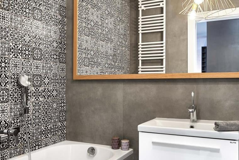 ŚCIANĘ NAD WANNĄ wyłożono niewielkimi płytkami zwzorem inspirowanym hiszpańską mozaiką (Max-Fliz). Wminimalistycznie zaaranżowanym pomieszczeniu takie kafelki stanowią niebanalny iwyrazisty akcent dekoracyjny. Pozostałe ściany, obudowę wanny oraz podłogę obłożono płytkami imitującymi beton (zarówno one, jak i armatura pochodzą z firmy Max-Fliz). Drobny ornament nie zaburza stylu wnętrza, ale ciekawie urozmaica jego dość surowy wystrój.