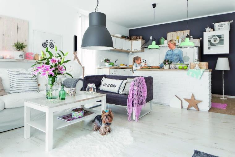 KUCHENNA WYSPA powstała z szafki z IKEA, którą od strony salonu gospodarze obłożyli cegłą. Biała zabudowa efektownie odcina się od ciemnej ściany.
