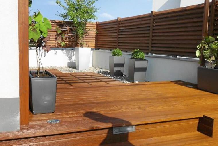 Rośliny balkonowe. Drewniane parawany, harmonizujące z podłogą, sprawiają, że na wysoko położonym tarasie jest zacisznie