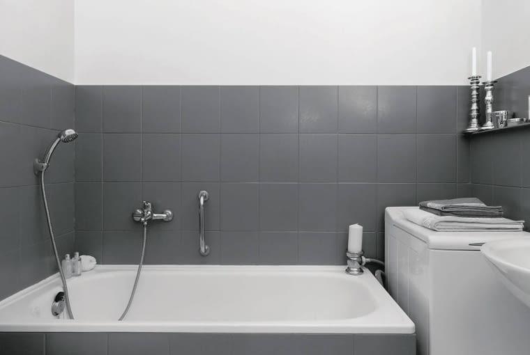 PO ZMIANIE. Jasna posadzka, pokryta farbą do płytek podłogowych, nie zmniejsza optycznie niespełna 6-metrowej łazienki. Znad wanny zniknęła zasłonka prysznicowa - gospodarze uznali, że nie jest im potrzebna.