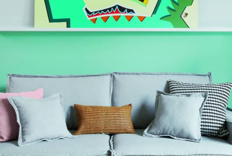 CO MA WISIEĆ... można oprzeć o ścianę. Specjalna półka zIKEA ma rant irowek, ustawiony na niej obraz się więc nie zsuwa. Kanapę zrobił na zamówienie tapicer. Szary mebel ładnie wygląda na tle kolorowej ściany.