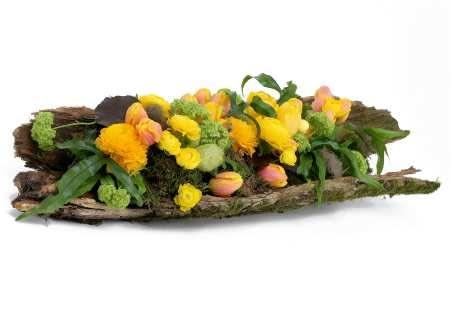 Również kawałek kory może stanowić naczynie. Świeżo i wiosennie będzie wyglądała wykonana w nim kompozycja z krótko przyciętych jaskrów, tulipanów, kaliny oraz owoców trojeści, liści paproci Pteris, galaksu i mchu.
