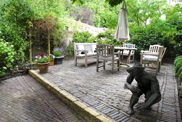 Postarzany ogród.Nawierzchnię ogrodowego tarasu ułożono ze starej cegły. Ciemne malarskie odcienie klinkieru budują szczególny nastrój tego wnętrza