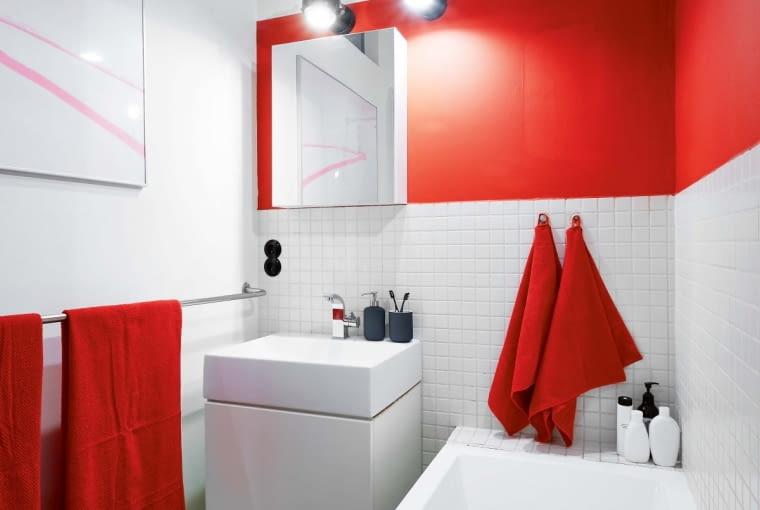 Mocna czerwień pojawiła się także w łazience. Pas na ścianie i dodatki przełamują sterylną biel i surowość geometrycznych form. Współczesne reflektorki z Castoramy nawiązują do projektów z lat sześćdziesiątych. Na ścianie grafika Janka Zamojskiego. Przedwojenne płytki (gorseciki) idealnie wkomponowały się we współczesny wystrój.