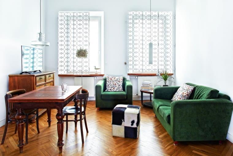 WIĘKSZOŚĆ MEBLI to odzyskane perełki sprzed lat. Eklektyczny dębowy stół zlat 30., krzesła, fotel irozkładaną kanapę właścicielka kupiła na olx.pl. Stolik kawowy (pod oknem) znalazła na strychu rodzinnego domu, komodę sprezentowali jej przyjaciele.