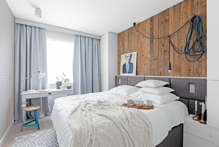 Drewniana okładzina ścienna to jeden z powtarzających się motywów w aranżacji mieszkania. W sypialni przybrała ona głębszą, cieplejszą barwę, która pięknie wydobywa usłojenie starych desek.