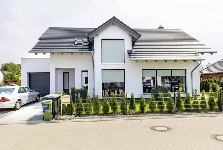 Elewacja: biały tynk; Dach: grafitowy; Okna, drzwi, brama garażowa: profile i skrzydła w kolorze szarym, kontrastującym z elewacją, harmonijnie komponującym się z dachem