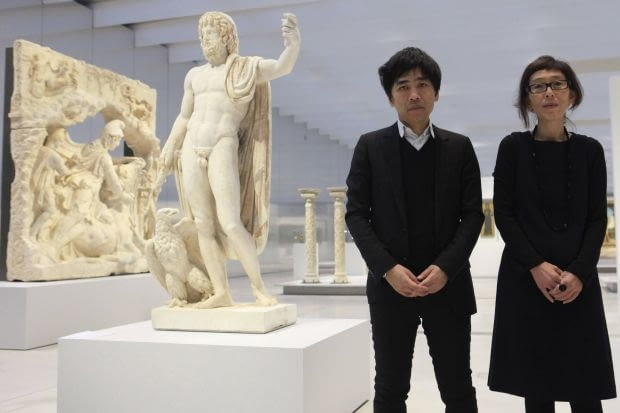 """Japanese architects Kazuyo Sejima (R) and Ryue Nishizawa (L) pose near the statue """"Jupiter, King of the Roman Gods carrying a thunderbolt and accompanied by an eagle"""" on the eve of the inauguration of Le Louvre Lens Museum in Lens, northern France, December 3, 2012. REUTERS/Pascal Rossignol (FRANCE - Tags: SOCIETY TRAVEL)"""