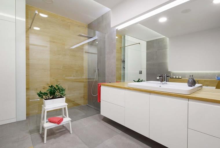 Jasne kolory, duże lustro, podwieszane szafki pod umywalką oraz przejrzysty parawan z hartowanego bezpiecznie tłukącego się szkła, który zabezpiecza wnętrze przed rozpryskiwaniem się wody spod prysznica, sprawiają, że wnętrze łazienki wydaje się bardzo przestronne i luksusowe
