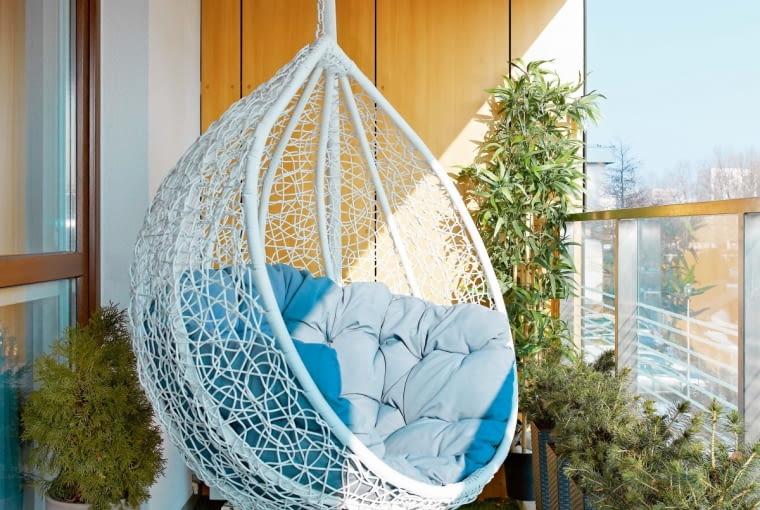 Na tych, którzy lubią bujać w obłokach, na balkonie czeka wiszący fotel-huśtawka (IKEA). Wykładzina imitująca trawę oraz żywe iglaki sprawiają, że nawet zimą jest tu zielono.