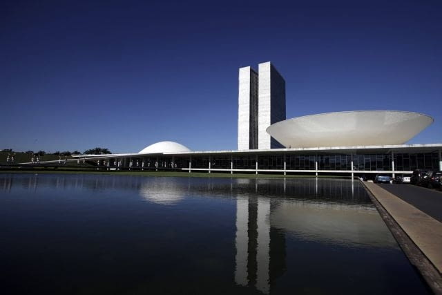 The Brazilian National Congress designed by architect Oscar Niemeyer is seen in Brasilia April 7, 2010. The dream was big. In just a few years, Brazil would build a modern capital in the middle of a savanna, an experiment in egalitarianism that would also shift power toward the center of the vast country. As Brasilia turned 50 years old on Wednesday, vestiges of that dream live on in Oscar Niemeyer's soaring architecture, the uniform residential apartment blocks, and the plane-like city shape that legend has it was meant to signal the Latin American giant's take-off. Picture taken April 7. To match Feature BRAZIL-BRASILIA/ REUTERS/Ricardo Moraes (BRAZIL - Tags: ANNIVERSARY CITYSCAPE)