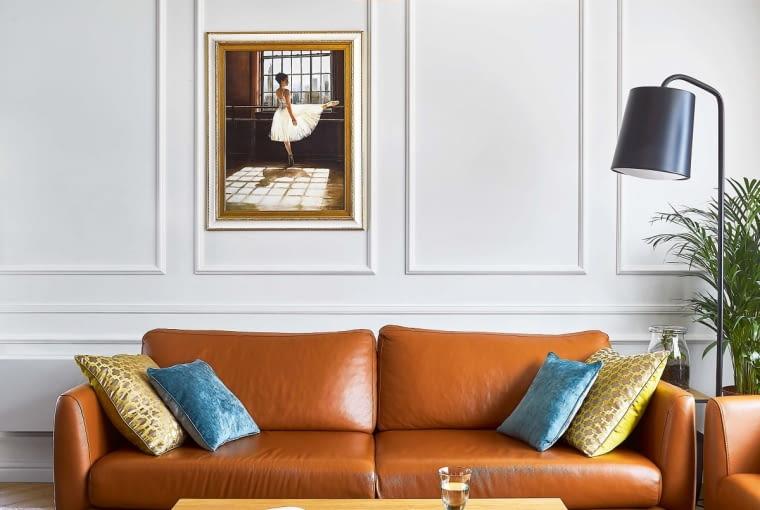 PRZYTULNOŚĆ I ELEGANCJA nie wykluczają się wzajemnie, czego dowodem jest salon. Szykownemu wnętrzu przytulności dodają poduchy, dywan, ciepłe odcienie sof (z BoConcept) i lamp (wisząca - z Flos, stojące - z Customform). Dobrze czułaby się tu baletnica z obrazu.