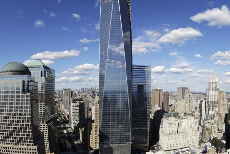 FILE - In this Thursday, Sept. 5, 2013, file photo taken with a fisheye lens, 1 World Trade Center, center, overlooks the wedge-shaped pavilion entrance of the National September 11 Museum, lower right, and the square outlines of the memorial waterfalls in New York. According to the nonprofit Council on Tall Buildings and Urban Habitat, 1 World Trade Center, once completed, will be the third tallest building in the world with a height of 1,776 feet. (AP Photo/Mark Lennihan, File)