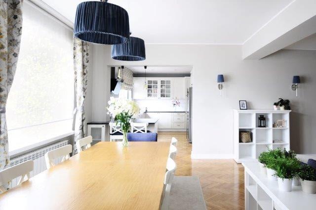 Jasne meble i ściany, plisowane, materiałowe abażury lamp i kwiecisty wzór zasłon wprowadzają sielankowy klimat do tej strefy domu. Ściany pomalowano delikatnym popielatym odcieniem. Granatowe kinkiety to powtarzalny element oświetlenia parteru.