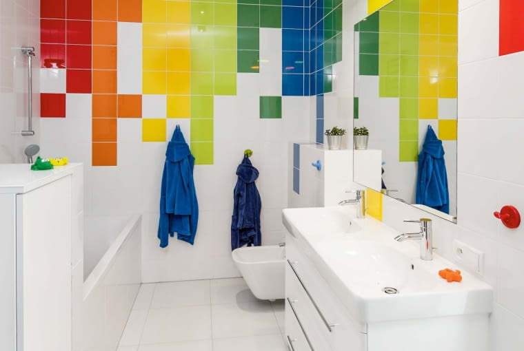 Ulokowana na końcu korytarza dziecięca łazienka jest ozdobiona ożywczą mozaiką kolorowych kafli