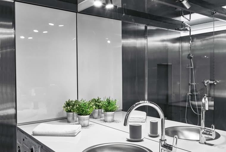 Aby optycznie powiększyć małą łazienkę, zastosowano w niej materiały odbijające światło. Ściany i sufit wyłożono stalą nierdzewną, a podłogę - aluminiową blachą ryflowaną. Natomiast ściana nad umywalką jest w całości pokryta lustrem. Kinkiety oświetlające przestrzeń wokół umywalki odbijają się w lustrze, przez co można odnieść wrażenie, że jest ich dwa razy więcej. Sprytnym rozwiązaniem jest zsyp na bieliznę. Dzięki otworowi w antresoli, do którego wrzuca się brudną odzież, nie trzeba nosić jej po schodach - ubrania same trafiają z garderoby do kosza pomysłowo ukrytego w szafie tuż obok pralki. Umywalka i bateria to starsze modele marki Grohe - pan domu kupił je po okazyjnej cenie w jednym ze sklepów internetowych.