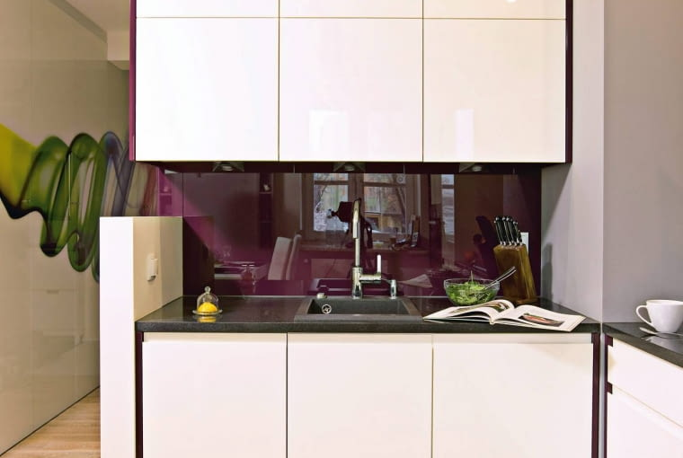 Białe meble kuchenne i fioletowe ściany