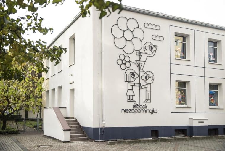 Odnowiony żłobek w Gdyni. Oszczędna w formie fasada, a na niej ilustracja metaloplastyczna zdradzająca funkcje budynku