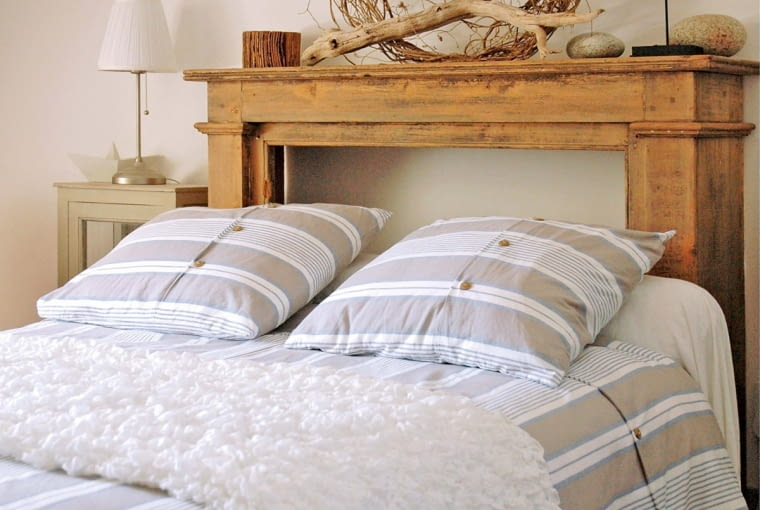 _Large bed with a wooden head and striped bed linen into a beige bedroom Palix Flore/Oredia