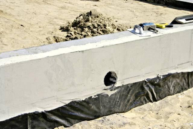 W ścianie fundamentowej należy zostawić otwory, przez które później przeprowadzi się rury