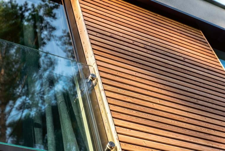 Barierka w oknach pokoi to tafla szkła przytwierdzona w czterech punktach do ramy okiennej. Na zdjęciu można także zaobserwować jak dobrze łączą się naturalne materiały - modrzew syberyjski ze szkłem i aluminium.