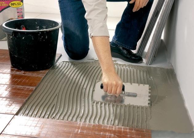Przy przyklejaniu płytek podłogowych wystarczy rozprowadzić klej na tylko podłożu