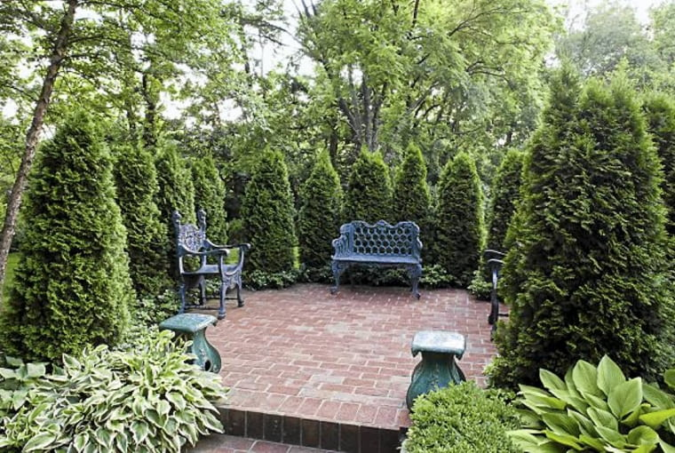 Patio surrounded by arborvitae (Thuja), Louisville, KY, USA