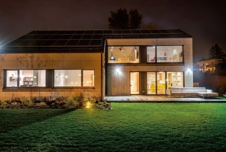 Okna z widokiem na ogród zajmują ? wysokości ścian na parterze i piętrze. Zgodnie z wymogami budownictwa niskoenergetycznego zostały zaplanowane od strony południowo-zachodniej, aby jak najwięcej ciepła i naturalnego światła docierało do domowych wnętrz